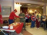 Commandant Erickson presenting the youngest Marine Cake.JPG